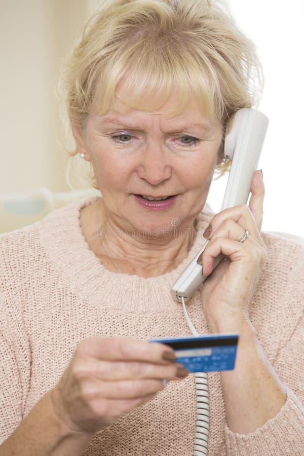 Mujer mayor que da los detalles de la tarjeta de crédito en el teléfono fotos de archivo libres de regalías
