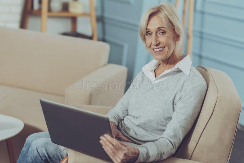 Mujer mayor que descansa con el ordenador portátil imágenes de archivo libres de regalías
