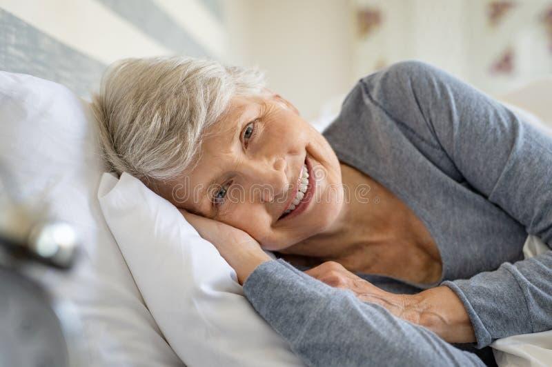 Mujer mayor que descansa sobre cama imagen de archivo libre de regalías