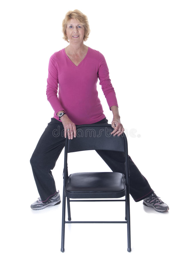Mujer mayor que ejercita con la silla imagen de archivo libre de regalías