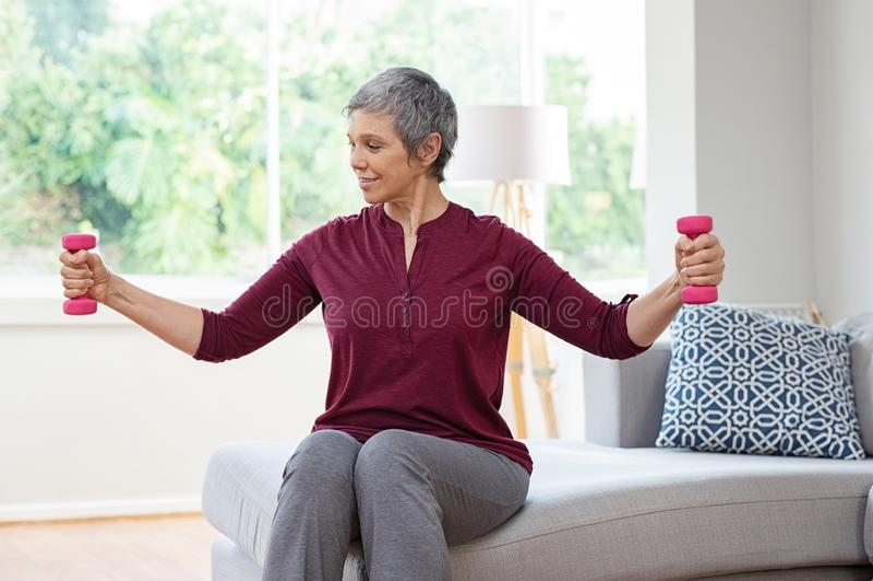 Mujer mayor que ejercita con pesas de gimnasia fotografía de archivo