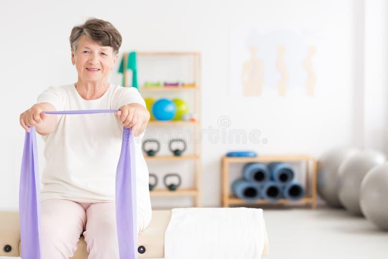 Mujer mayor que ejercita en el gimnasio imagen de archivo