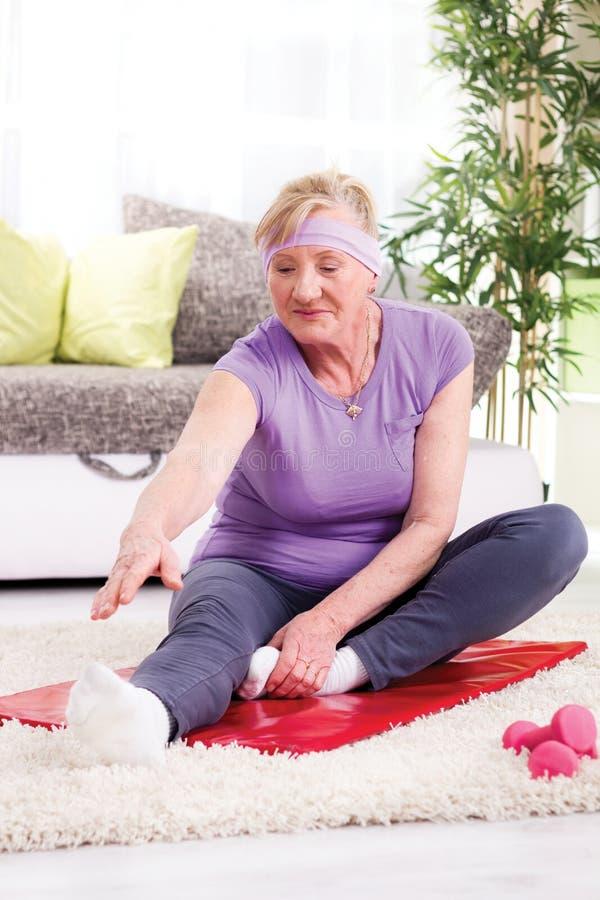 Mujer mayor que ejercita en el gimnasio casero fotos de archivo libres de regalías