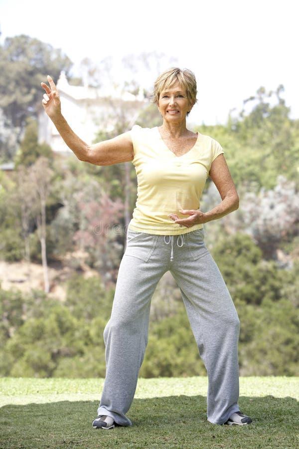 Mujer mayor que ejercita en parque foto de archivo