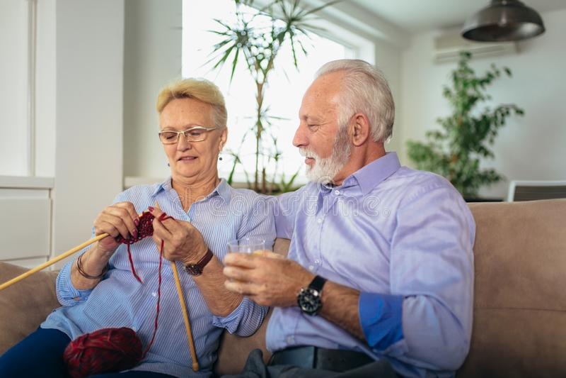 Mujer mayor que ense?a su marido al arte de hacer punto la ropa de lana fotos de archivo