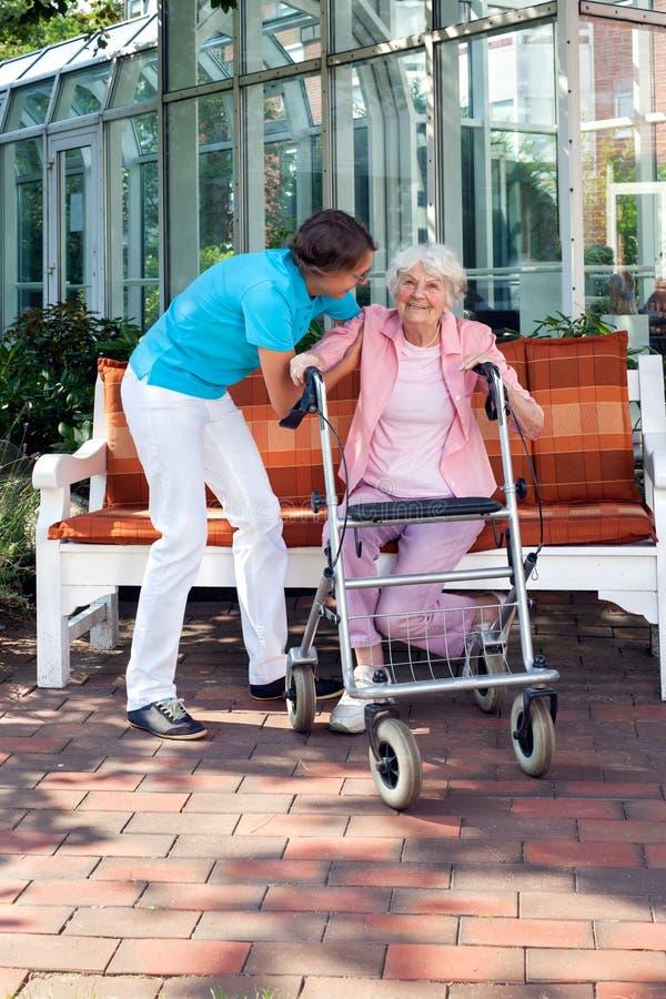 Mujer mayor que es ayudada por un ayudante del cuidado imagen de archivo