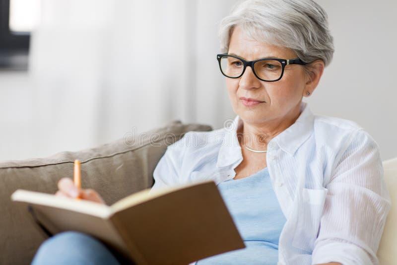Mujer mayor que escribe al cuaderno o al diario en casa fotografía de archivo libre de regalías