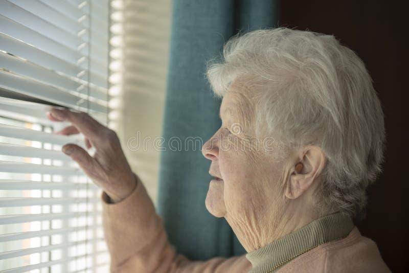 Mujer mayor que esp?a a trav?s de ventana fotografía de archivo libre de regalías