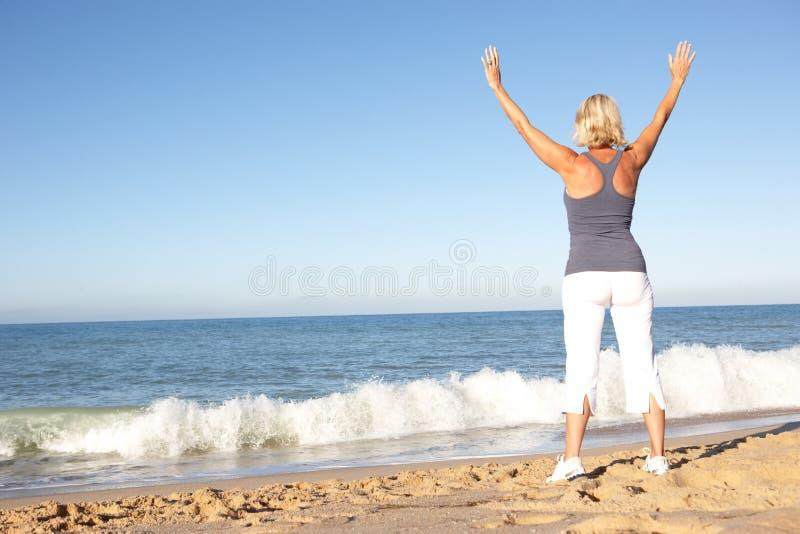 Mujer mayor que estira en la playa foto de archivo