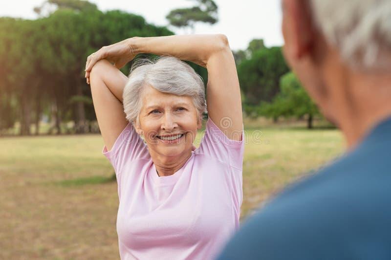 Mujer mayor que estira los brazos foto de archivo libre de regalías