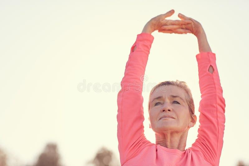 Mujer mayor que estira los brazos antes de exerci al aire libre de la madrugada imagen de archivo