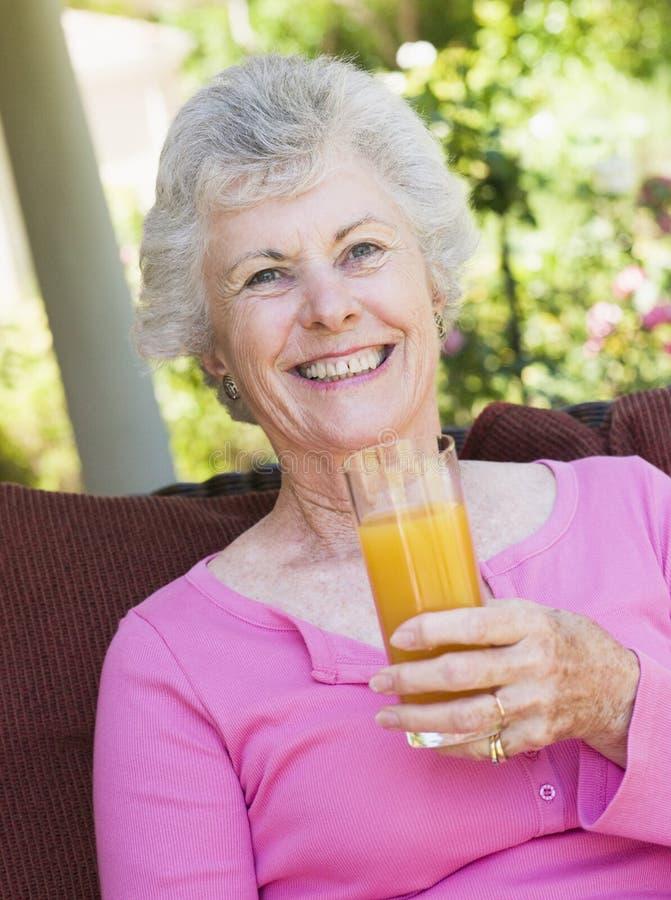 Mujer mayor que goza del vidrio de jugo imágenes de archivo libres de regalías