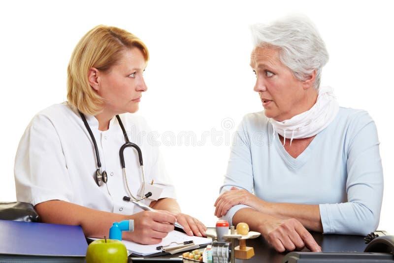 Mujer mayor que habla con el doctor imagen de archivo libre de regalías