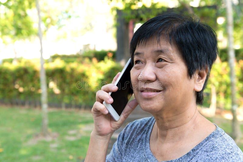 Mujer mayor que habla en el teléfono elegante foto de archivo