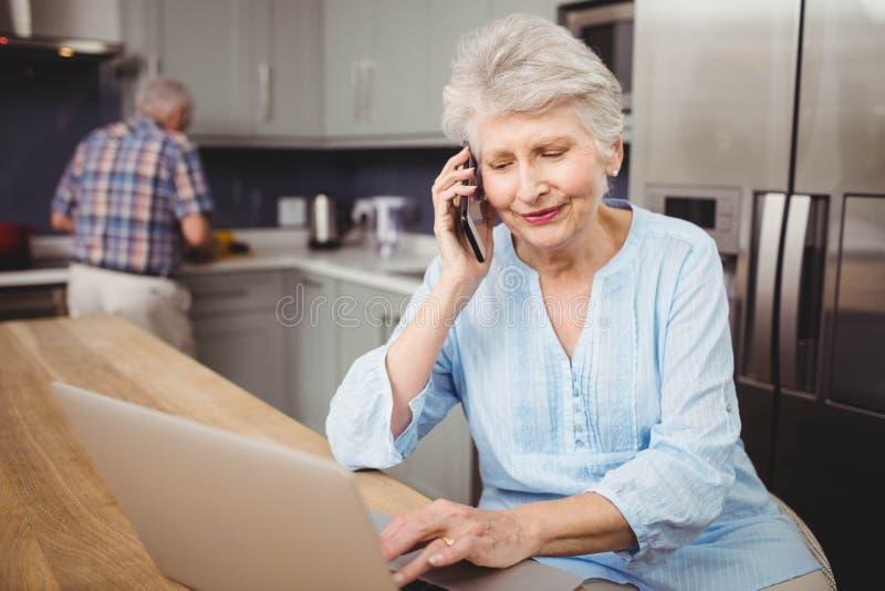 Mujer mayor que habla en el teléfono mientras que usa el ordenador portátil y al hombre que trabajan en cocina imagenes de archivo