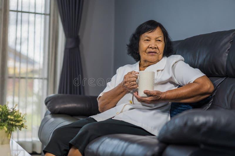 Mujer mayor que habla y que bebe una taza de agua foto de archivo libre de regalías