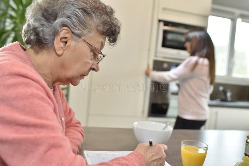 Mujer mayor que hace crucigramas en la cocina fotografía de archivo libre de regalías