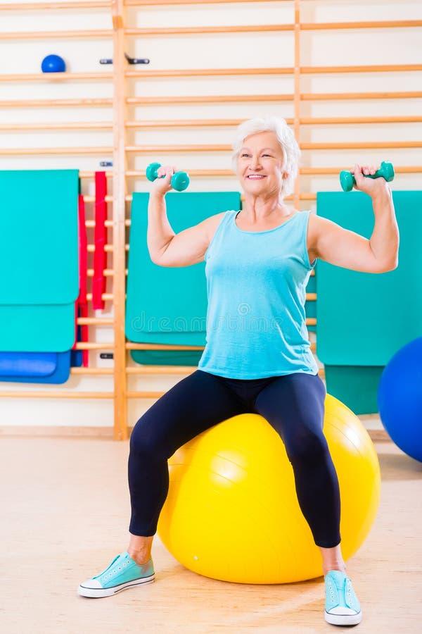 Mujer mayor que hace deporte de la aptitud en gimnasio fotografía de archivo