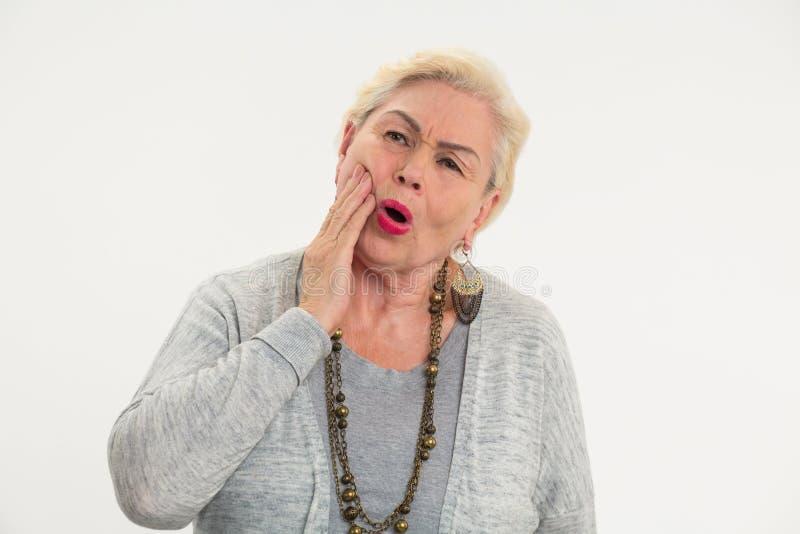 Mujer mayor que hace dolor de muelas aislar imagenes de archivo