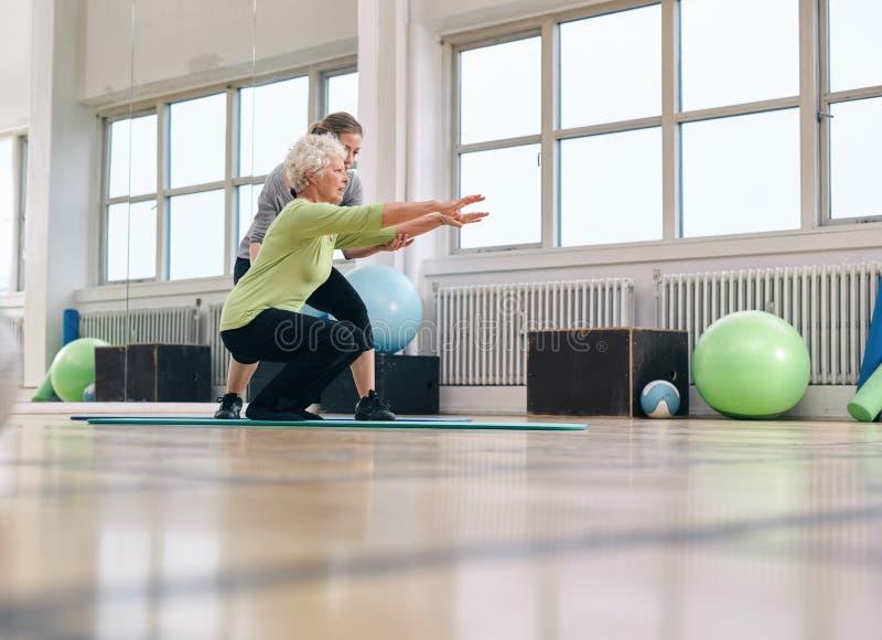 Mujer mayor que hace ejercicio con su instructor personal imagen de archivo libre de regalías