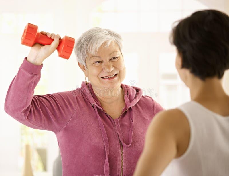 Mujer mayor que hace ejercicio de la pesa de gimnasia imagen de archivo