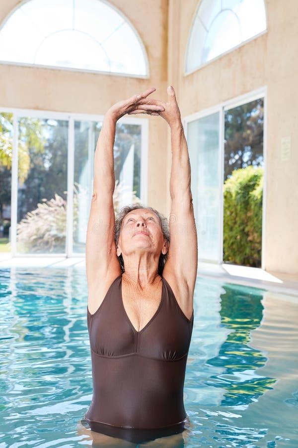 Mujer mayor que hace ejercicio que estira sano imagenes de archivo