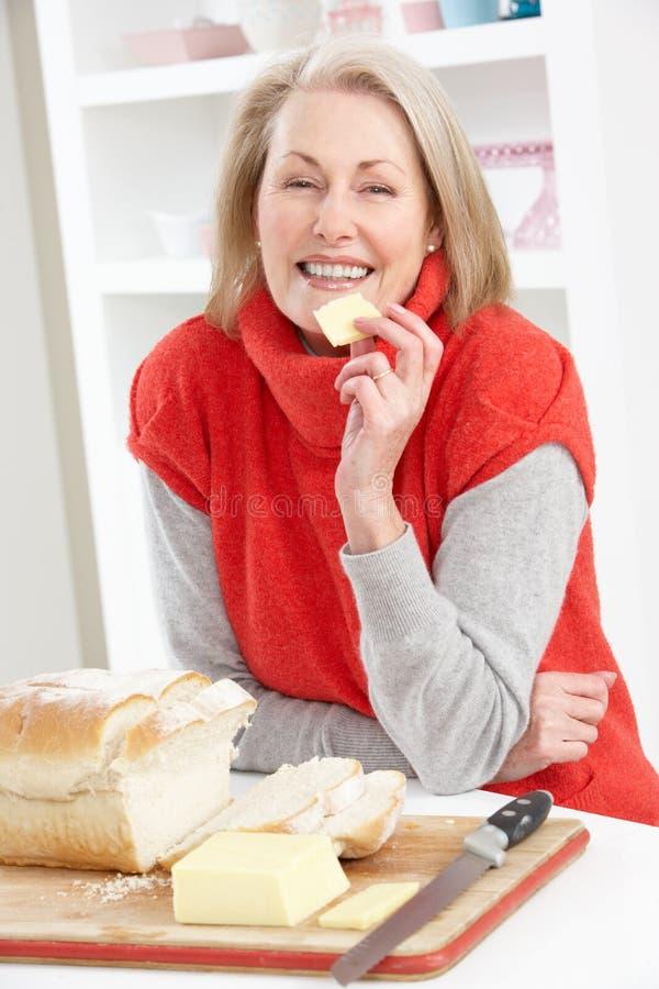 Mujer mayor que hace el emparedado en cocina foto de archivo