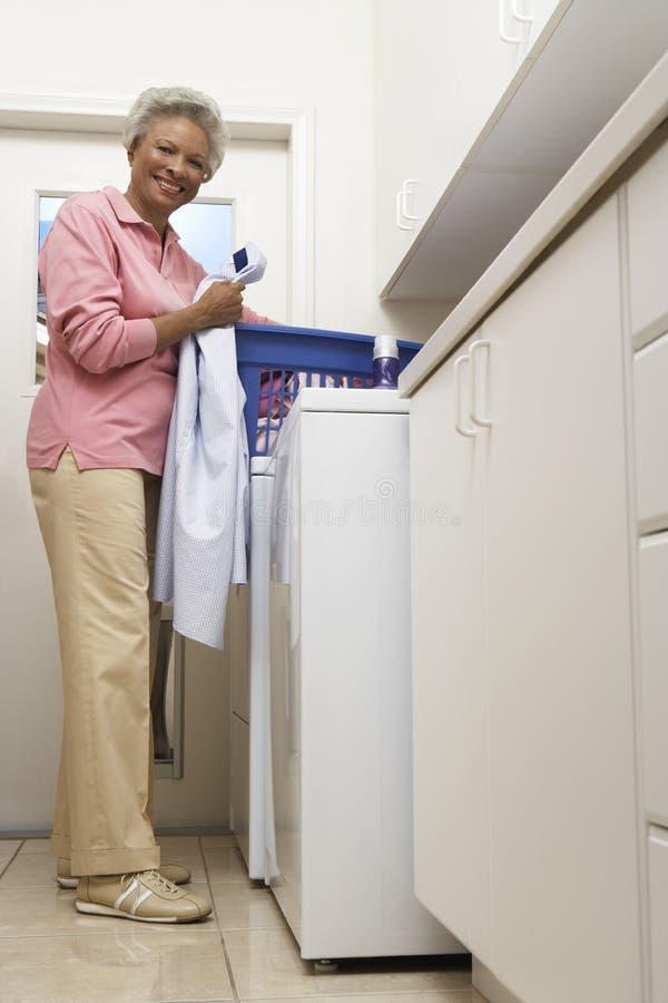 Mujer mayor que hace el lavadero en casa imagenes de archivo