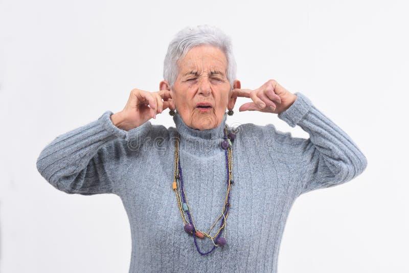 Mujer mayor que hace el ruido que daña sus oídos en el fondo blanco foto de archivo