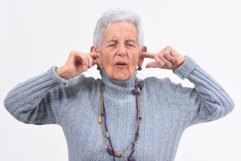 Mujer mayor que hace el ruido que daña sus oídos en el fondo blanco imagenes de archivo