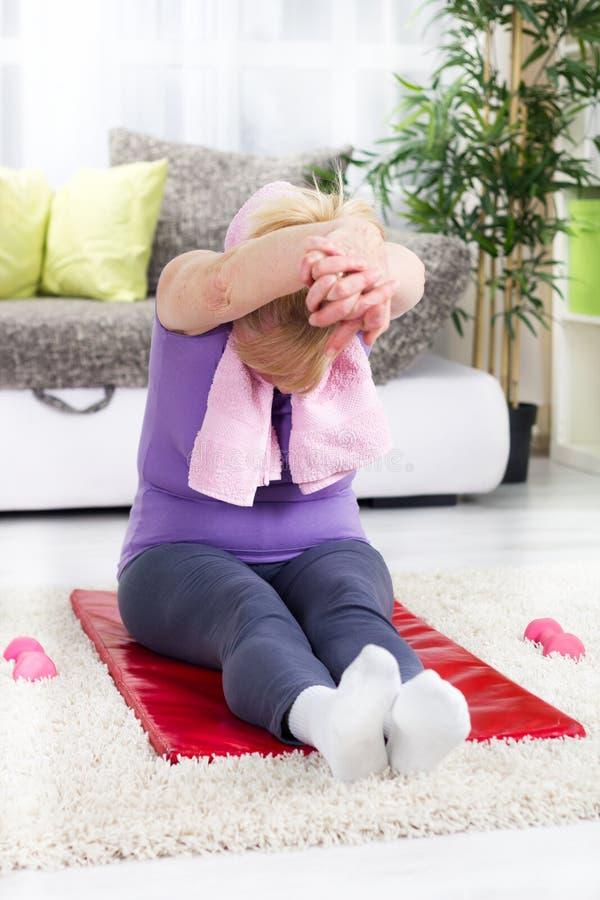 Mujer mayor que hace estirando ejercicios imágenes de archivo libres de regalías