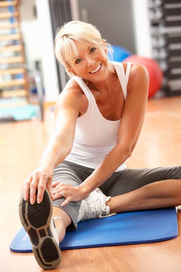 Mujer mayor que hace estirando ejercicios en gimnasia imagen de archivo