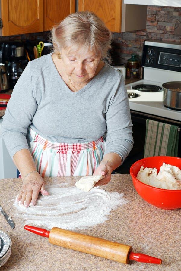 Mujer mayor que hace la empanada fotografía de archivo