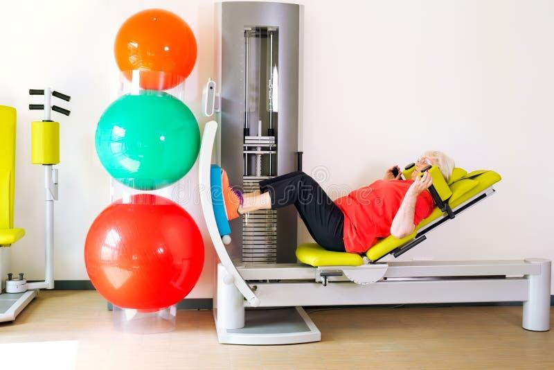 Mujer mayor que hace la pierna que consolida ejercicios fotos de archivo libres de regalías