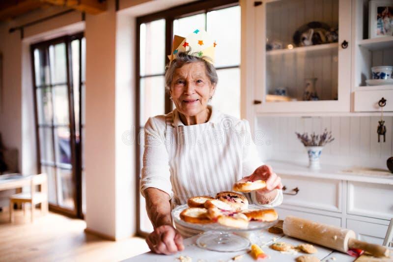 Mujer mayor que hace las tortas en una cocina en casa Copie el espacio fotos de archivo