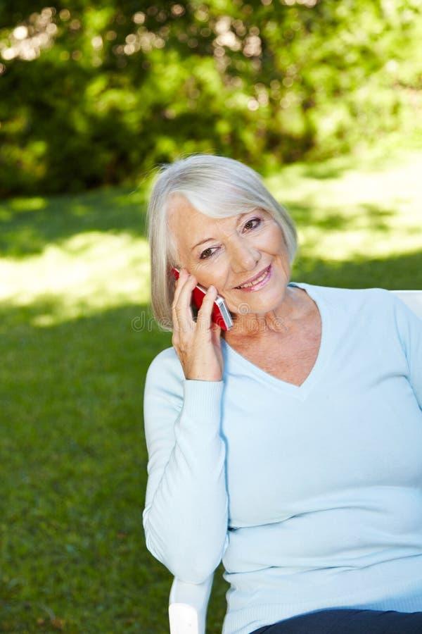 Mujer mayor que hace llamada con smartphone imagen de archivo