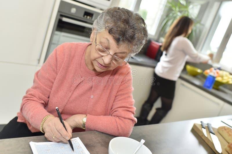 Mujer mayor que hace los crucigramas que esperan la comida imagenes de archivo