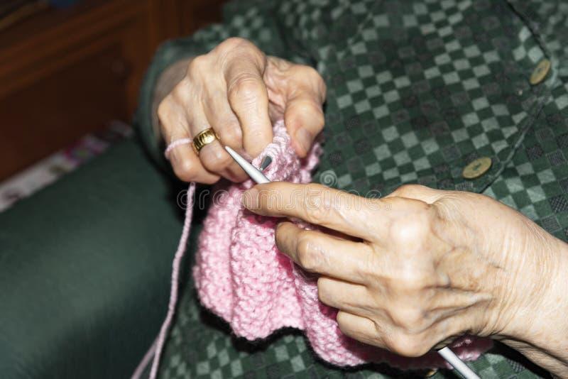 Mujer mayor que hace punto en casa fotografía de archivo