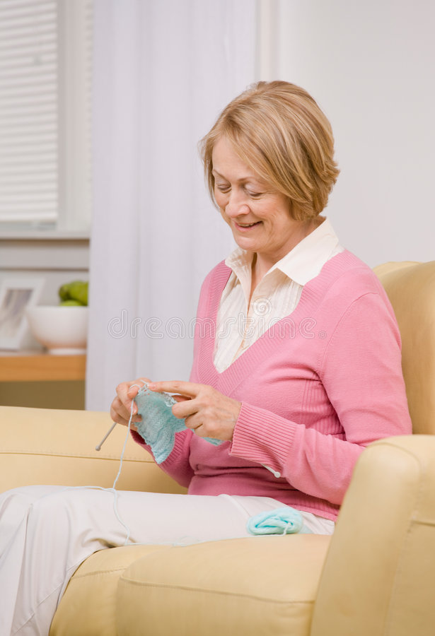 Mujer mayor que hace punto en el sofá en el país fotografía de archivo