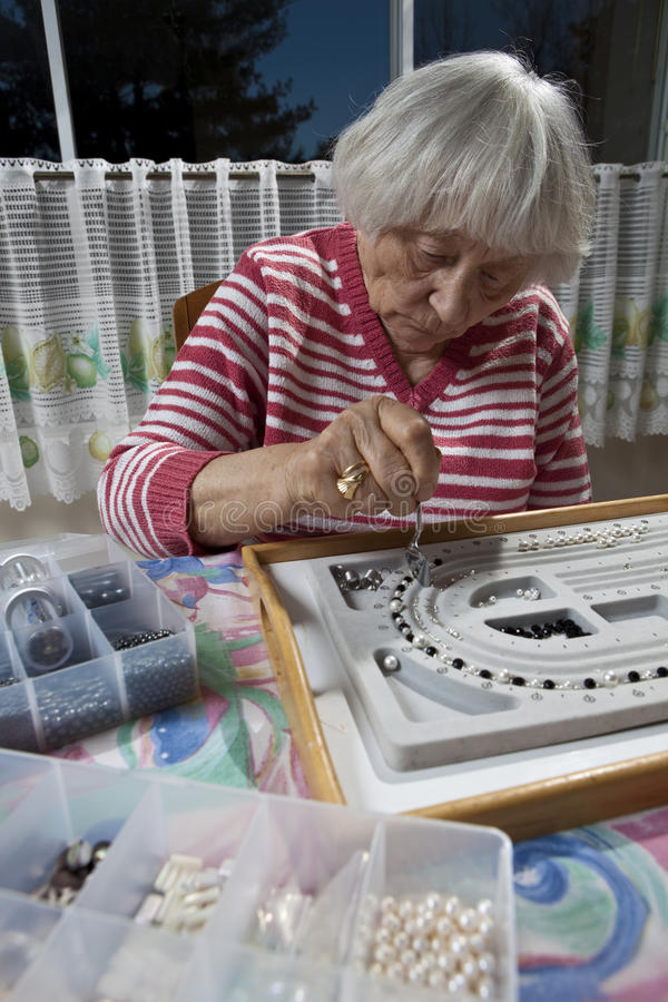 Mujer mayor que hace un collar fotos de archivo