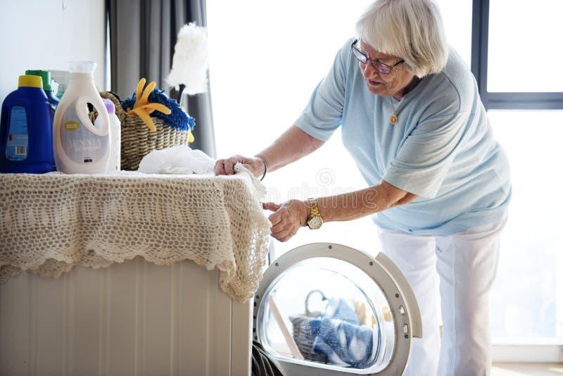 Mujer mayor que hace un lavadero imagen de archivo libre de regalías