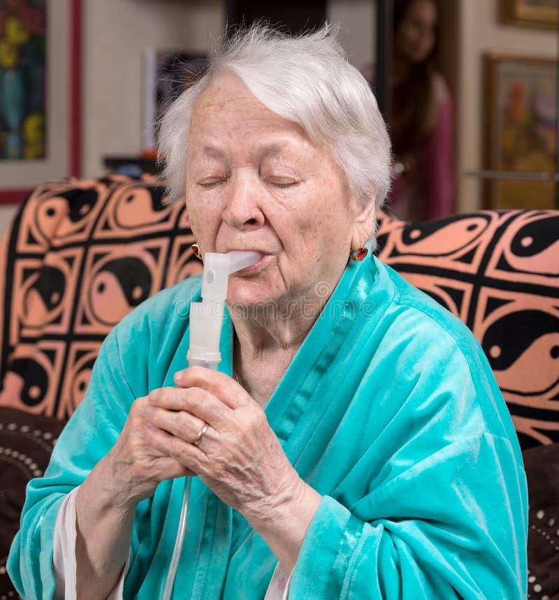 Mujer mayor que hace una inhalación fotos de archivo libres de regalías
