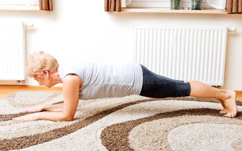 Mujer mayor que hace yoga en sala de estar fotos de archivo