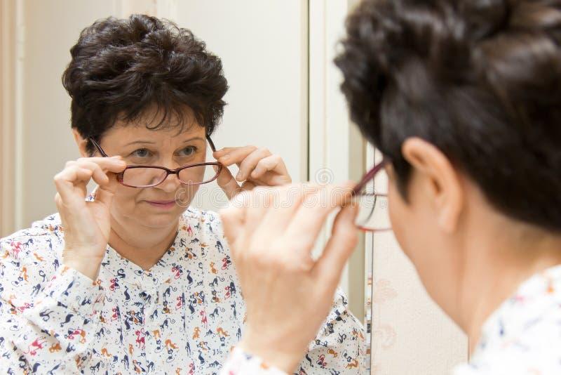 Mujer mayor que intenta en las nuevas lentes y que mira sobre los vidrios en el espejo imágenes de archivo libres de regalías