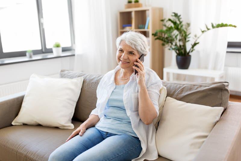 Mujer mayor que invita a smartphone en casa fotos de archivo libres de regalías
