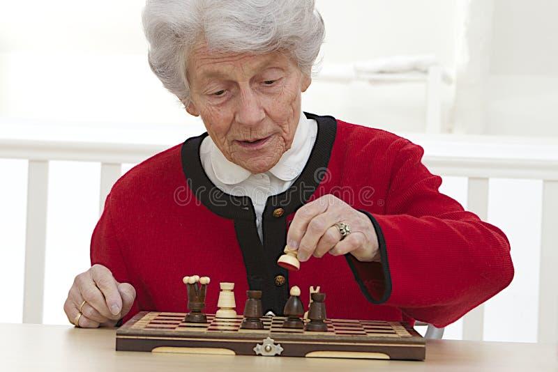 Mujer mayor que juega en la casa de retiro imagen de archivo