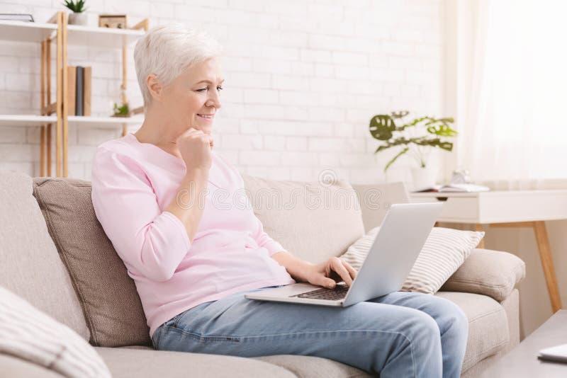Mujer mayor que juega a los videojuegos en su ordenador portátil imágenes de archivo libres de regalías