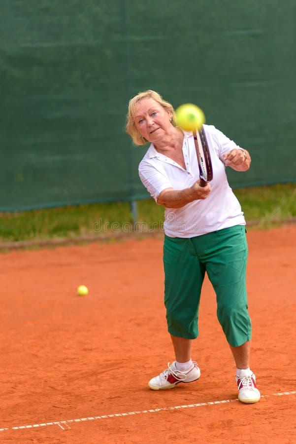 Mujer mayor que juega a tenis fotografía de archivo libre de regalías