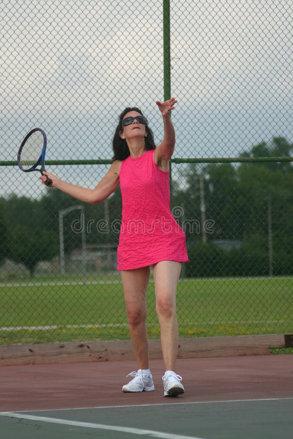 Mujer mayor que juega a tenis foto de archivo
