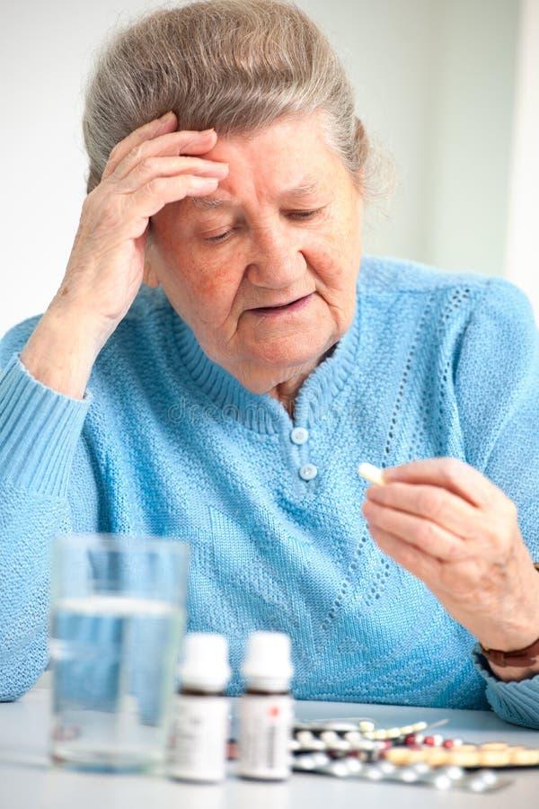 Mujer mayor que le toma la medicina fotos de archivo